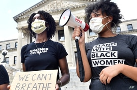 Protesters, who did not wish to be identified, chant outside the Mississippi State Capitol building in Jackson, Miss.