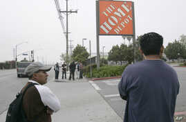 Only a few day laborers seek work near a skilled labor site at a Home Depot in Glendale, Calif.
