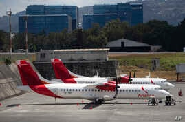 Aircraft from the Avianca airline sit parked at La Aurora airport in Guatemala City, Tuesday, March 17, 2020.