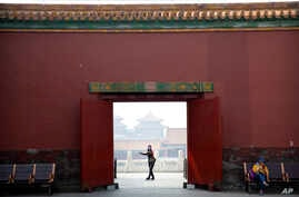 A visitor wearing a face mask to protect against the new coronavirus walks through the Forbidden City in Beijing, Friday, May 1…