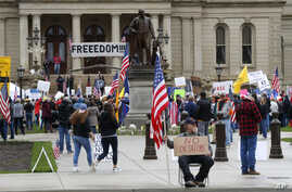 Protesters rally at the State Capitol in Lansing, Mich, April 30, 2020. Gun-carrying protesters have been a common sight at some demonstrations calling for coronavirus-related restrictions to be lifted.