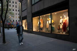 A man wearing a mask walks by a window display at a J Crew store in Rockefeller Center, May 2, 2020, in New York.