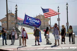 Protesters wave flags in front of the pier, May 3, 2020, in Huntington Beach, Calif.