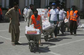 Volunteers deliver food relief packages for the Muslim fasting month of Ramadan, during a government-imposed nationwide lockdown to help contain the spread of the new coronavirus, in Peshawar, Pakistan, May 4, 2020.