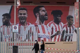 Two women wearing face masks pass by a giant poster of Atletico Madrid soccer players at the Wanda Metropolitano stadium