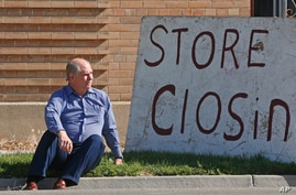 """Euro Treasures Antiques owner Scott Evans poses next to his """"store closing"""" sign Friday, May 8, 2020, in Salt Lake City."""