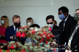 Staff members wear masks as they listen to President Donald Trump speak about the coronavirus during a press briefing in the…