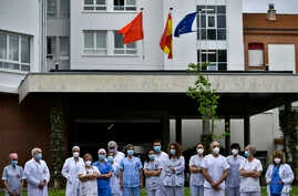 Health services staff members stand outside at Navarra Hospital in a two minute silence in tribute for members of staff who died of coronovirus, in Pamplona, northern Spain, May 14, 2020.