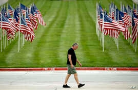 A man walks past a row of flags as he visits a park, Friday, May 15, 2020, in Kansas City, Missouri.