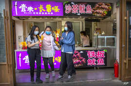 People wearing face masks to protect against the spread of the new coronavirus buy snacks at a shop in Beijing.
