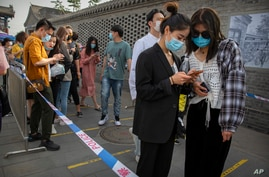 People wearing face masks to protect against the new coronavirus use their smartphones to enter their personal data