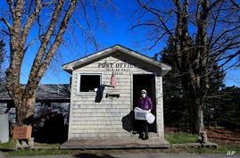Postmistress Donna DeWitt carries mail at the tiny post office on Isle Au Haut, Maine. The post office serves the 70 or so year-round island residents, May 6, 2020.