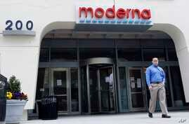 A man stands outside an entrance to a Moderna, Inc., building, May 18, 2020, in Cambridge, Mass. Moderna announced Monday that an experimental vaccine against the coronavirus showed encouraging results in very early testing.
