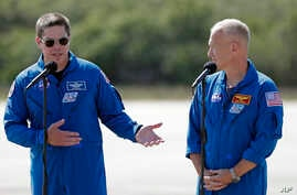 NASA astronauts Robert Behnken, left, and Doug Hurley speak during a news conference after they arrived at the Kennedy Space…