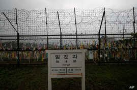 A directional sign showing the distance to N. Korea's Kaesong city and S. Korea's capital Seoul is seen near the wire fences decorated with ribbons written with reunification wishing at the Imjingak Pavilion in Paju, S. Korea, May 26, 2020.