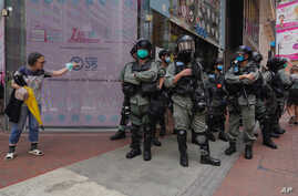 Riot police stand guard as a woman tries to cross the street in the Causeway Bay district of Hong Kong