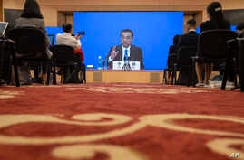 Chinese Premier Li Keqiang speaks on screen during a press conference by video conferencing at the end of the National People's Congress in Beijing on Thursday, May 28, 2020.