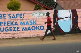 A young boy walks past a wall with graffiti urging people to wear face masks in Harare, Thursday, May, 28, 2020. Manhunts have…