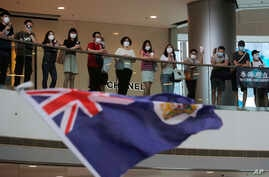 "Protesters sing ""Glory to Hong Kong"" and wave a Hong Kong colonial flag in a shopping mall during a protest against China's national security legislation for the city, in Hong Kong, Friday, May 29, 2020."