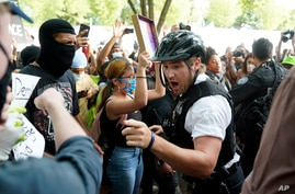 Demonstrators argue with uniformed U.S Secret Service police officers during a protest about the death of George Floyd