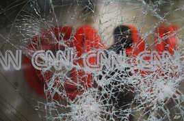 A security guard walks behind shattered glass at the CNN building at the CNN Center in the aftermath of a demonstration