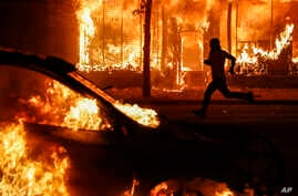 A protester runs past burning cars and buildings on Chicago Avenue, May 30, 2020, in St. Paul, Minn.