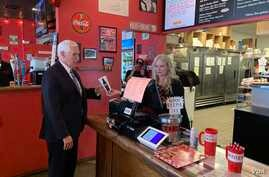 U.S. Vice President Mike Pence orders lunch from Beth Steele, owner of Beth'a Burger Bar in Orlando, Florida on May 20, 2020. (P