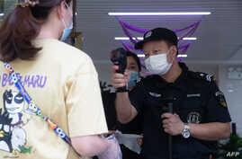 A security guard checks the body temperature of a woman in Wuhan in China's central Hubei province, May 11, 2020.