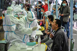 A medical worker takes a swab sample from a resident to be tested for the COVID-19 in Wuhan in China's central Hubei province.