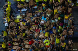 FILE - A photo taken on March 27, 2020, shows prison inmates, some resting, others gesturing, in cramped conditions in the crowded courtyard of the Quezon City jail in Manila, Philippines.