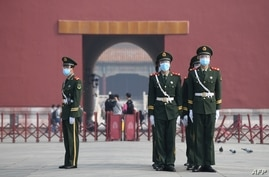 FILE - Paramilitary police officers wear face masks and goggles amid concerns of the COVID-19 coronavirus as they stand guard outside the Forbidden City, the former palace of China's emperors, in Beijing, May 1, 2020.