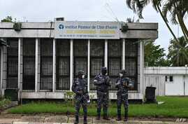 FILE - Police officers wearing face masks stands outside the Pasteur Institute of Ivory Coast, near Abidjan, May 11, 2020.