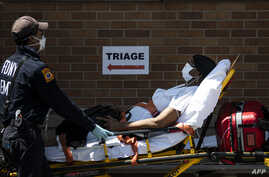 FILE - A medical worker transports a patient outside a special COVID-19 area at Maimonides Medical Center, in the Brooklyn borough of New York City, May 17, 2020.