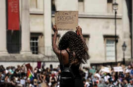 A woman holds up a banner as people gather in Trafalgar Square in central London, May 31, 2020, to protest against the recent killing of George Floyd by police officers in Minneapolis that has led to protests across the U.S.