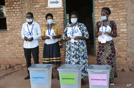Electoral officials wearing face masks to protect against the coronavirus, stand by ballot boxes before voters cast their votes in a presidential election, in Giheta, Gitega province, Burundi, May 20, 2020.