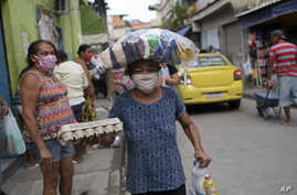 "A woman wearing a protective face mask carries food donated by ""Eu sou Eu"" or ""I am me,"" a non-profit run by former inmates, during the coronavirus pandemic, at the Para-Pedro favela in Rio de Janeiro, Brazil, May 8, 2020."