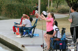 FILE - A girl checks her line as people fish at Veterans Oasis Park in Chandler, Arizona, April 30, 2020, a popular activity during the coronavirus pandemic.