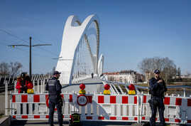 German police officers guard a closed bridge at the French-German border at the river Rhine in Kehl, Germany, March 16, 2020.