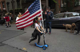 A girl parades up and down her block with a U.S. flag on her scooter, in the Greenwich Village neighborhood, during a partial easing of coronavirus restrictions in New York, May 14, 2020.