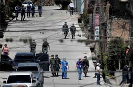 FILE - Workers from the Ministry of Health are accompanied by soldiers and police as they investigate in a cordoned off neighborhood after multiple people tested positive for the new coronavirus, in Tegucigalpa, Honduras, March 17, 2020.