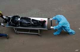 Hospital staff carry the body of a person who died of  COVID-19 to a morgue in Mumbai, India, May 29, 2020.