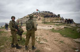 Israeli soldiers take position as Palestinian demonstrators gather during a protest against expansion of Israeli settlements, in the West Bank village of Beita near Nablus, March 2, 2020.