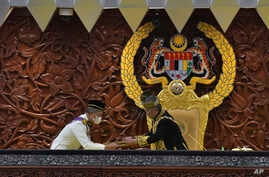 In this photo released by Malaysia's Department of Information, King Sultan Abdullah Sultan Ahmad Shah, right, receives documents from Prime Minister Muhyiddin Yassin during the parliamentary session in Kuala Lumpur, May 18, 2020.