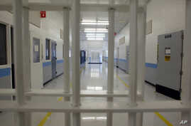 FILE - An empty corridor is seen a correctional facility in Baldwin, Michigan, Nov. 3, 2005. Plans for an immigrant detention center in Ionia, Michigan, have been suspended.