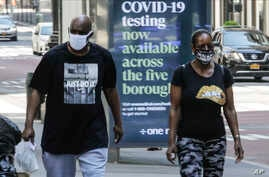 Pedestrians wear protective masks during the coronavirus pandemic, in New York City, May 15, 2020.