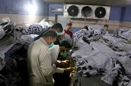 People identify the body of a relative, who was killed in Friday's plane crash, at a morgue in Karachi, Pakistan, May 23, 2020.