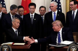 President Donald Trump shakes hands with Chinese Vice Premier Liu He, after signing a trade agreement in the East Room of the White House, Jan. 15, 2020, in Washington.