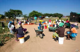 FILE - Women and children wait for their turn to fetch water in a poor suburb of Harare, Zimbabwe, March, 31, 2020.