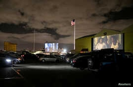 FILE - People inside their cars watch a movie at a drive-in theater while keeping social distancing rules amid the coronavirus pandemic, in Fort Lauderdale, Florida, March 28, 2020.