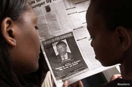 FILE - Women look at a newspaper June 12, 2002, in Nairobi, Kenya, featuring a photo of Rwandan businessman Felicien Kabuga, wanted in connection with Rwanda's 1994 genocide.